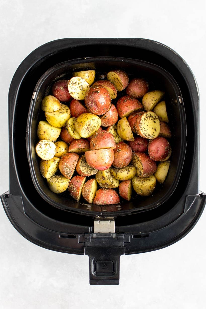 Raw potatoes tossed with dried herbs sitting in an air fryer basket.