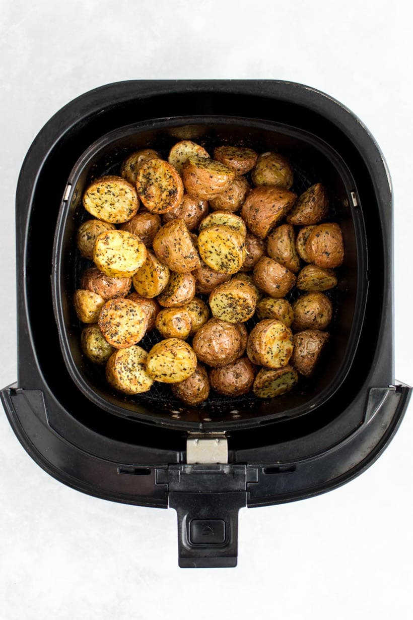Cooked crispy baby potatoes in an air fryer basket.