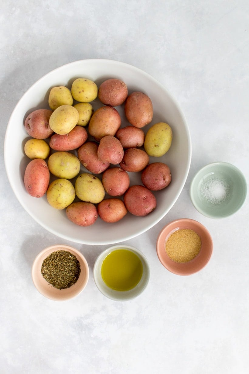 Baby potatoes in a bowl, along with four other small bowls filled with dried basil, olive oil, garlic powder, and salt.
