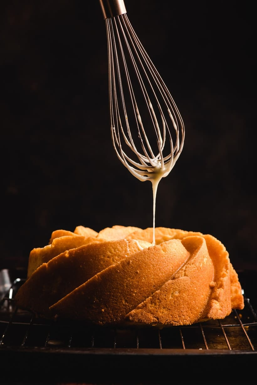 Whisk drizzling orange glaze over a bundt cake.
