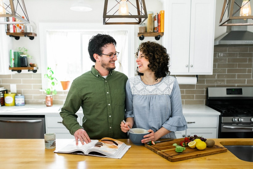 A man and woman standing next to each other in a kitchen, laughing.