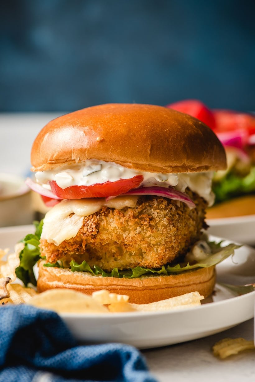 Crispy Cod Fish Sandwich with melted cheese, tomato, lettuce, and homemade tartar suace with a golden brioche bun.
