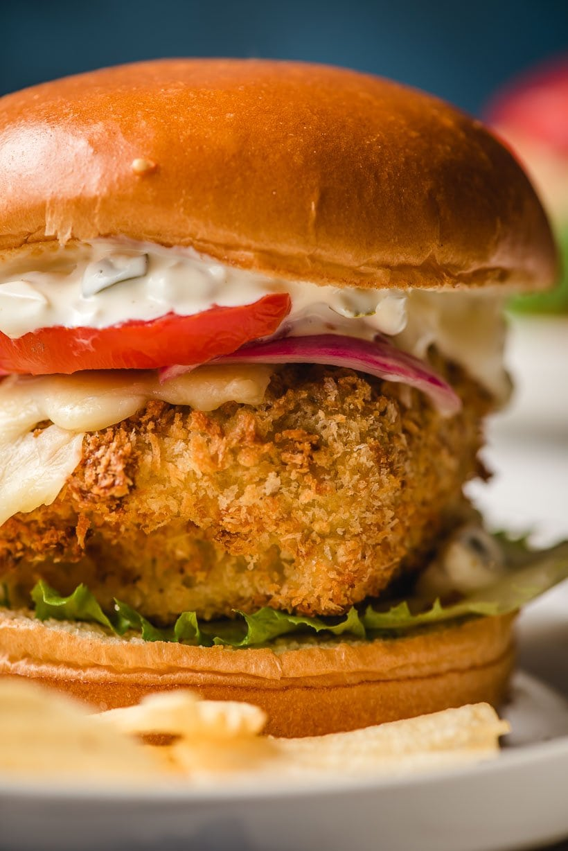 Up close image of air fryer fish sandwich topped with cheese, lettuce, tomato, onion, and tartar sauce.