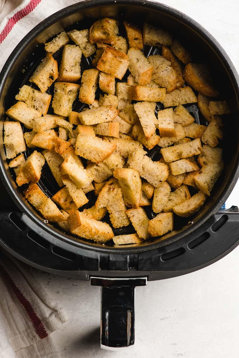 Air fryer basket filled with crunchy fried croutons.