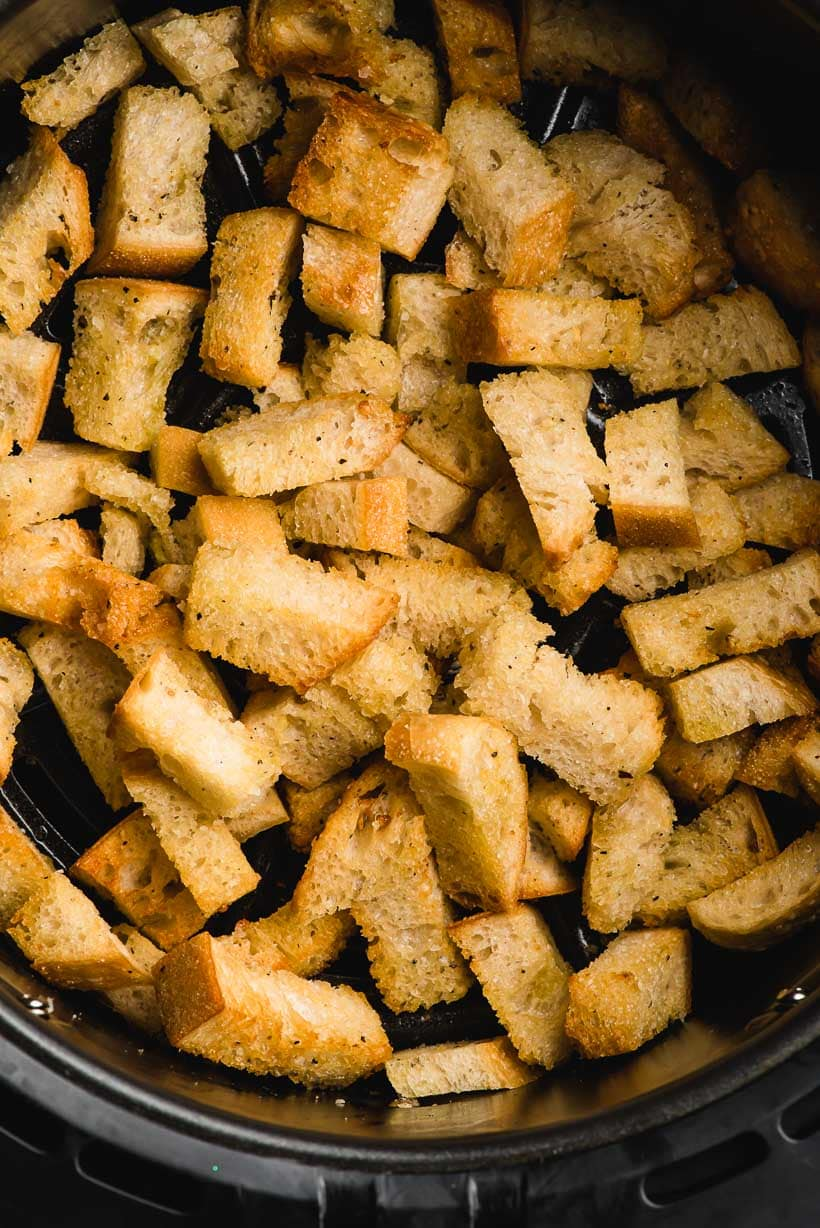 Air Fryer basket filled with air fried croutons.