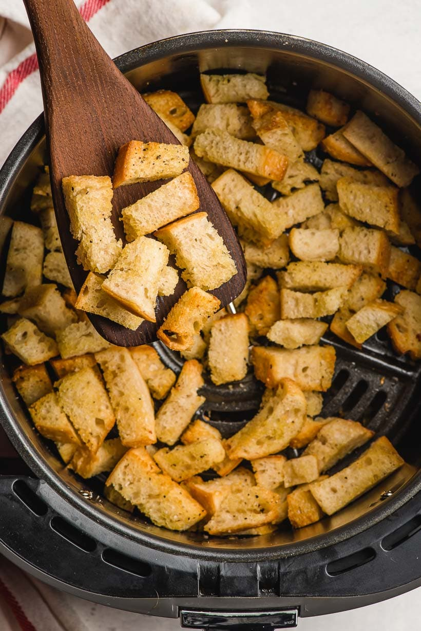 Wooden spatula scooping croutons out of an air fryer basket.
