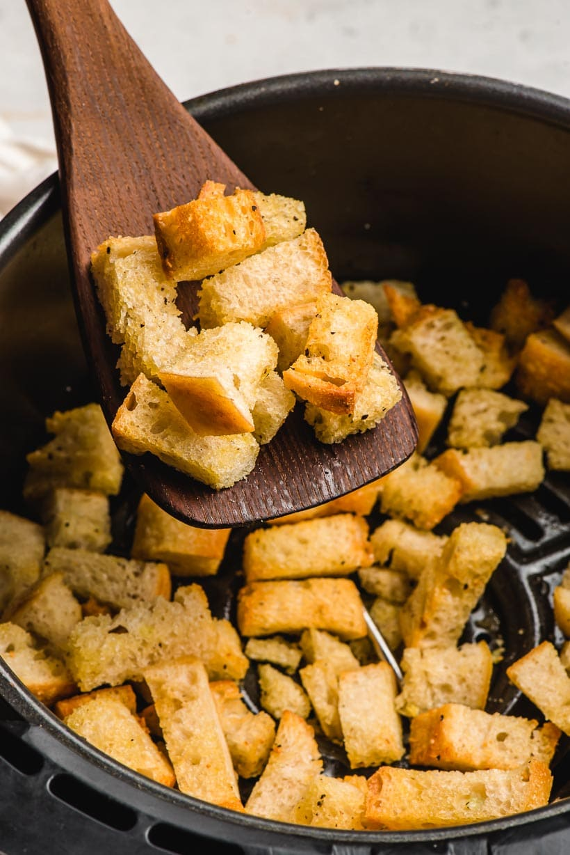 Wooden spatula holding air fried croutons above the air fryer basket.