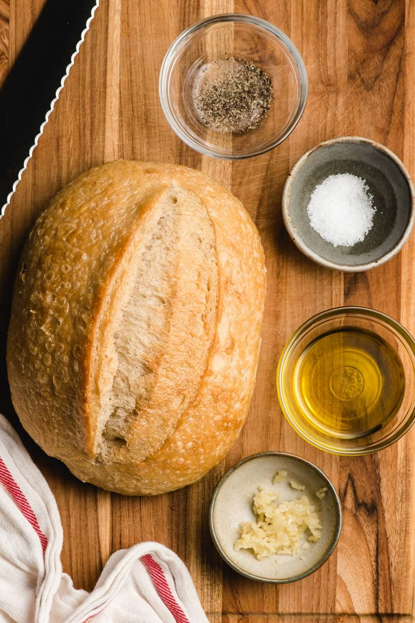 Loaf of bread surrounded by four small bowls filled with pepper, salt, olive oil, and garlic.