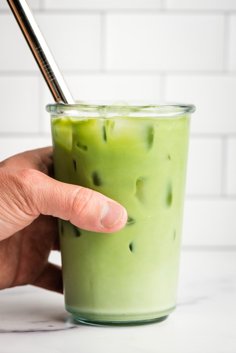 Hand holding a glass of iced matcha latte with a steel straw.