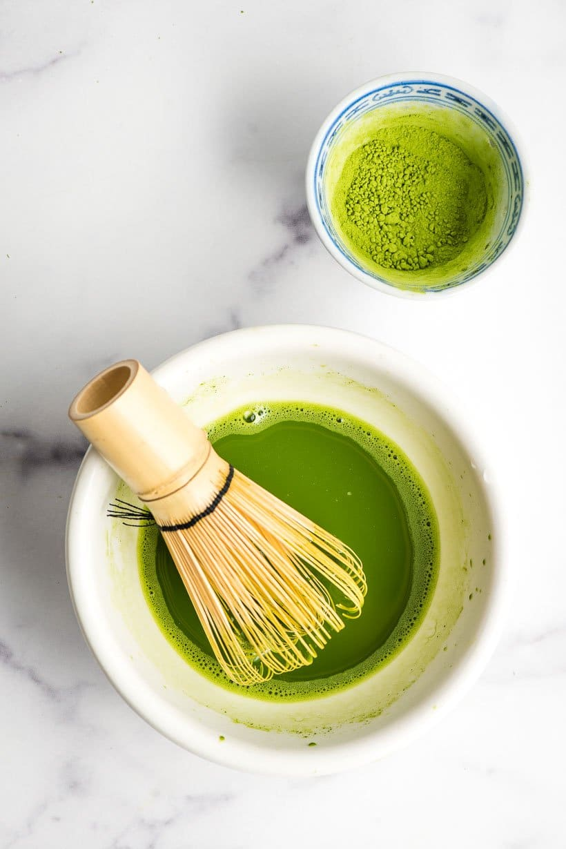 White bowl filled with matcha powder and water with a bamboo whisk.