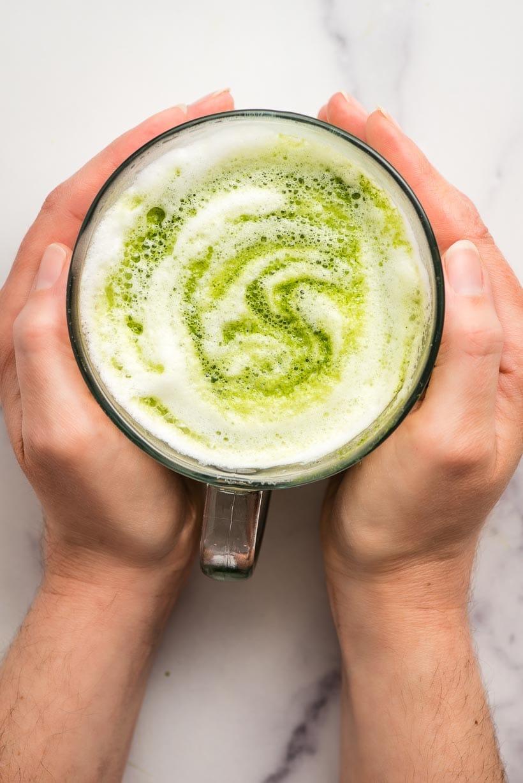 Hands holding a mug of hot matcha latte.