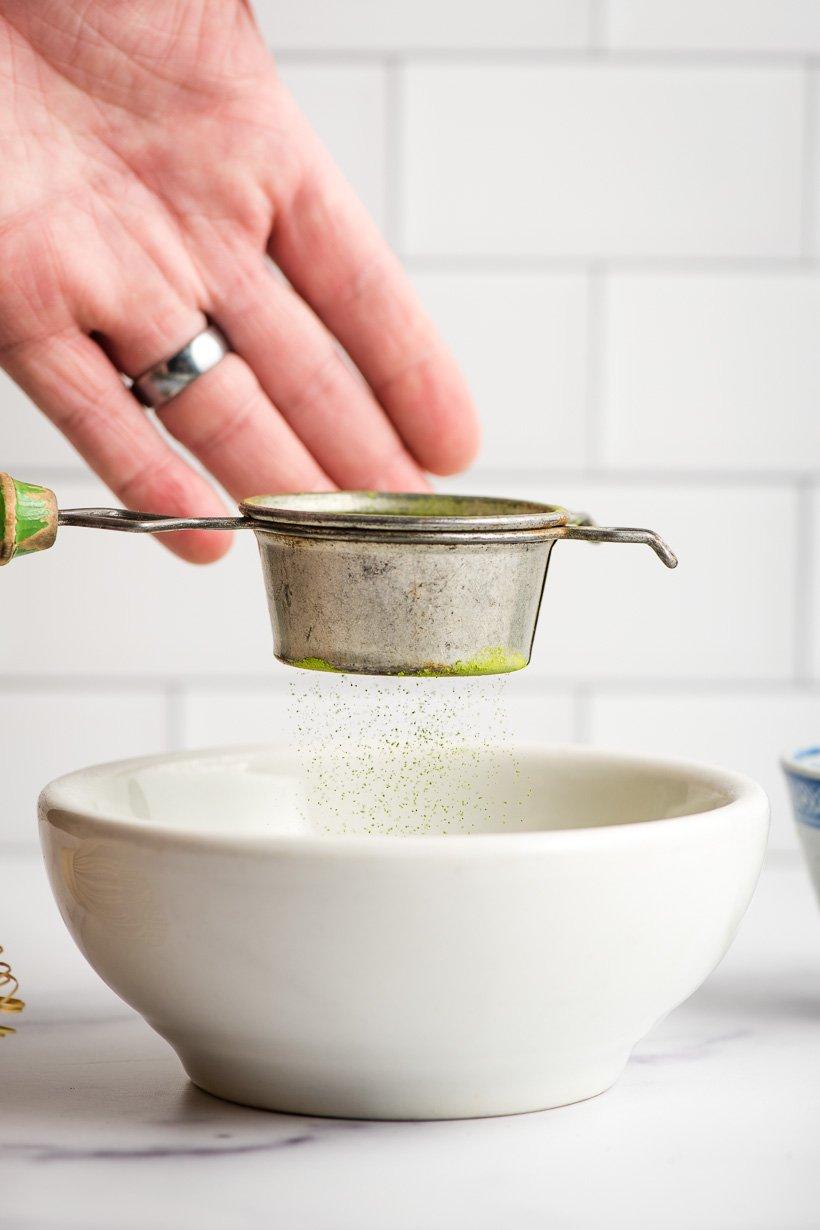 Hand sifting matcha powder into a small bowl.
