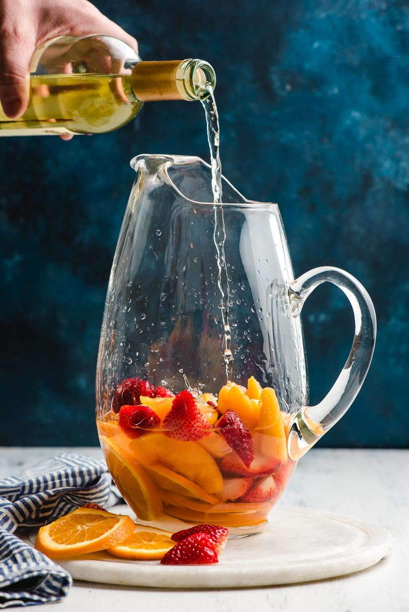 White wine being poured into a glass pitcher filled with strawberries, oranges, and peach slices.