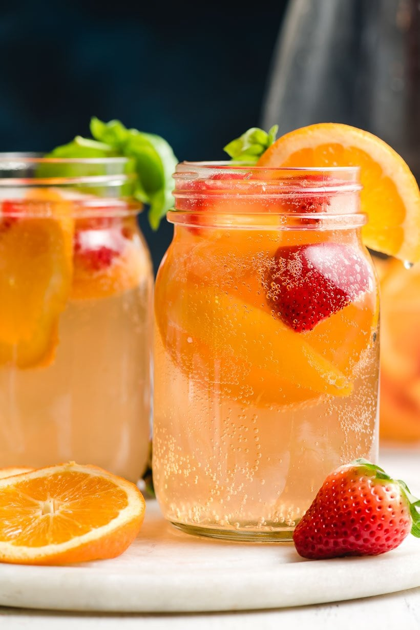Glass of summer sangria with peaches, strawberries, and oranges floating in the bubbly sangria.