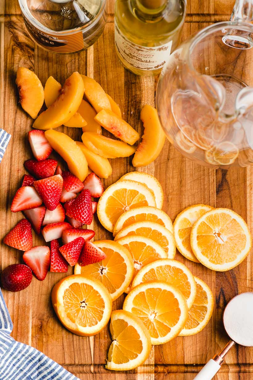 Sliced strawberries, oranges, and peaches arranged on a wood cutting board with orange liqueur and white wine bottles.