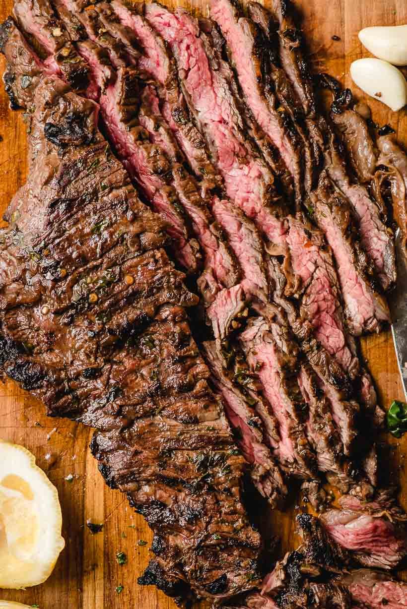 Grilled skirt steak on a wooden cutting board, half of it sliced into long, thin slices.