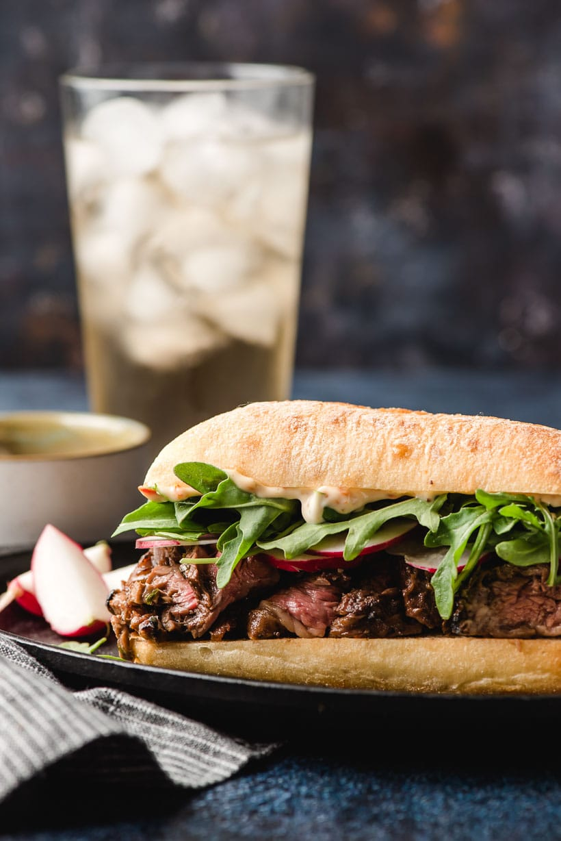 A skirt steak sandwich on a black plate with a glass of ginger ale in the background.