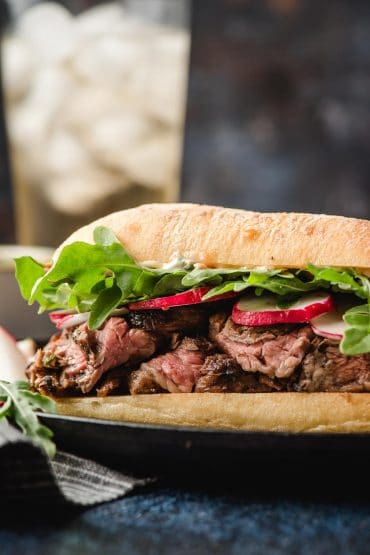 Steak sandwich on a ciabatta roll topped with arugula and sliced radishes.