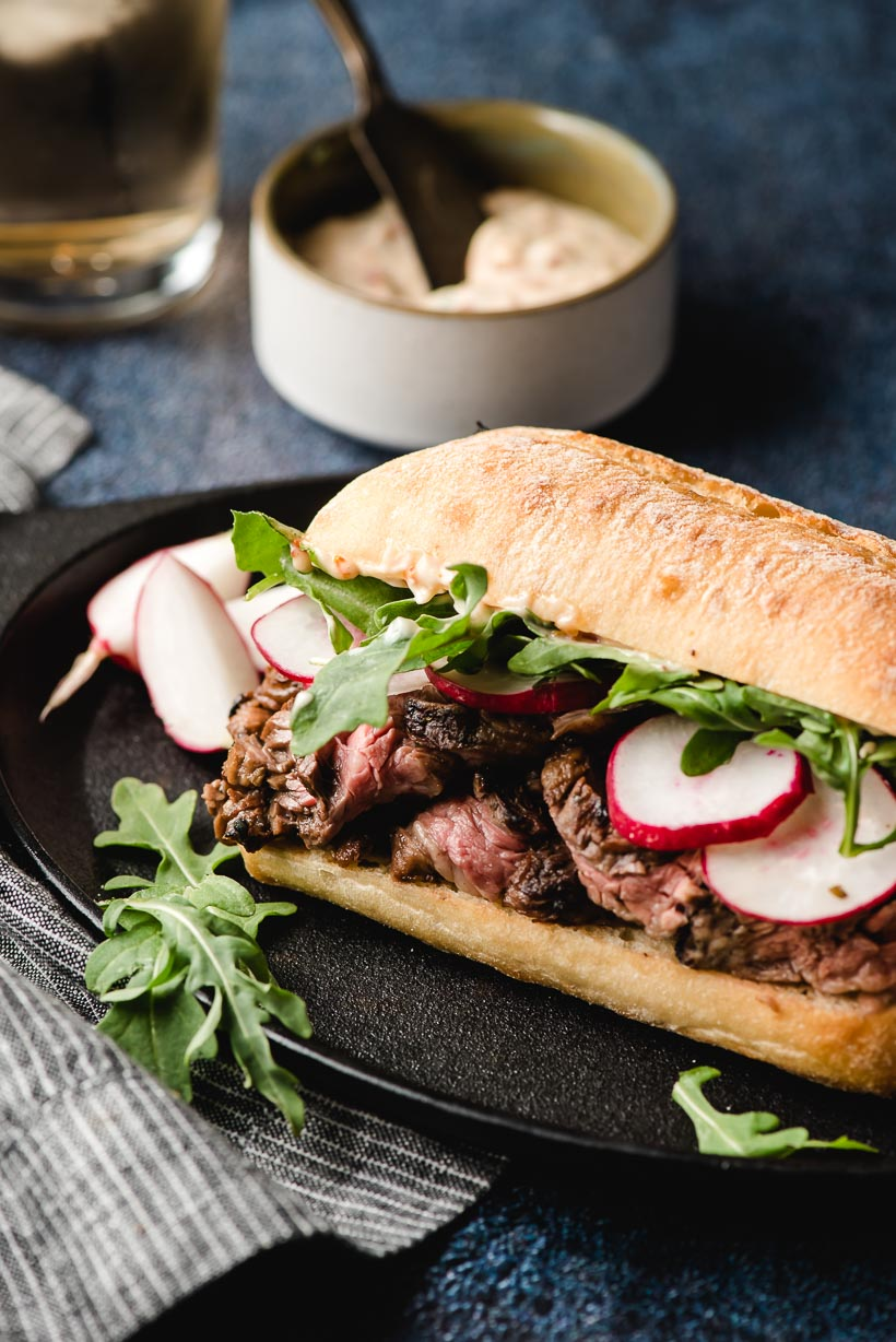 Skirt steak sandwich with arugula and radishes on a black plate.
