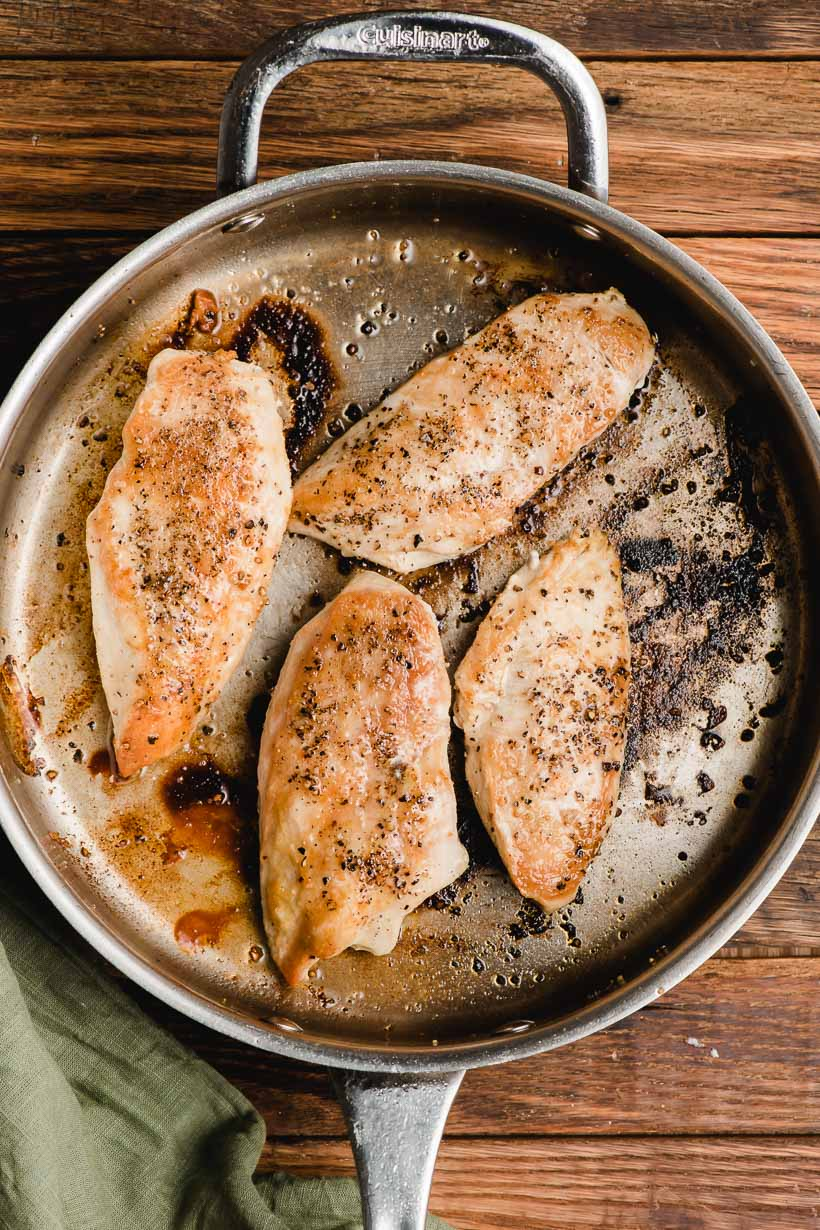 Seared chicken breasts shown in a deep skillet.