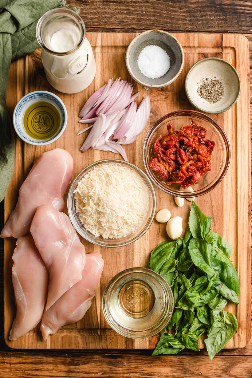 Ingredients for sun dried tomato chicken pasta displayed on a wooden cutting board.