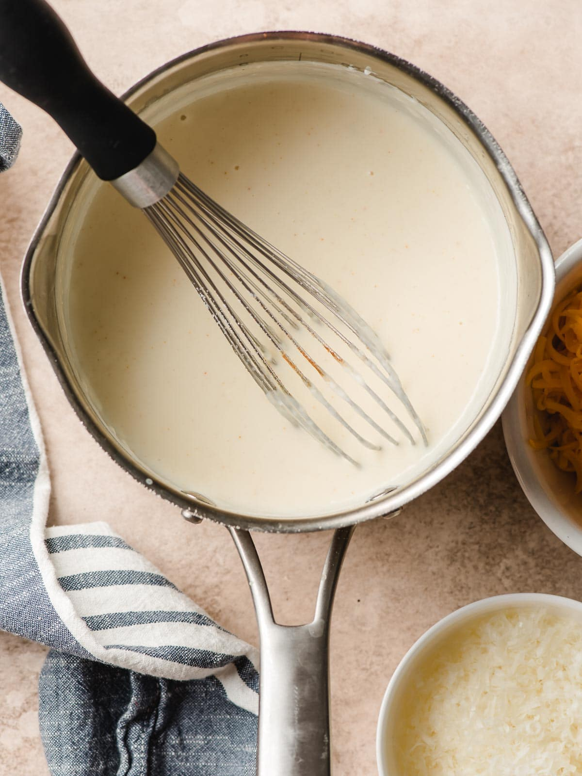 Bechamel sauce in a silver pot with a whisk propped inside.