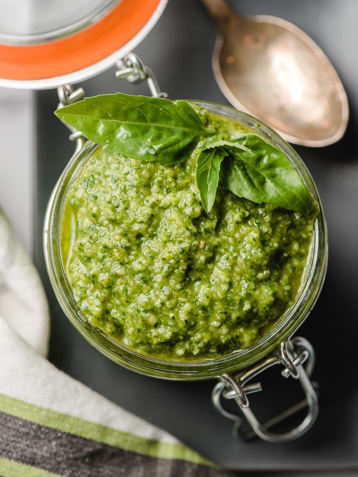 Pesto in a glass jar garnished with fresh basil leaf sprig.