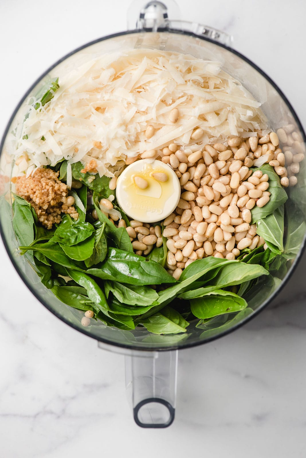 Basil, pine nuts, garlic, and Parmesan cheese shown in an open food processor bowl.