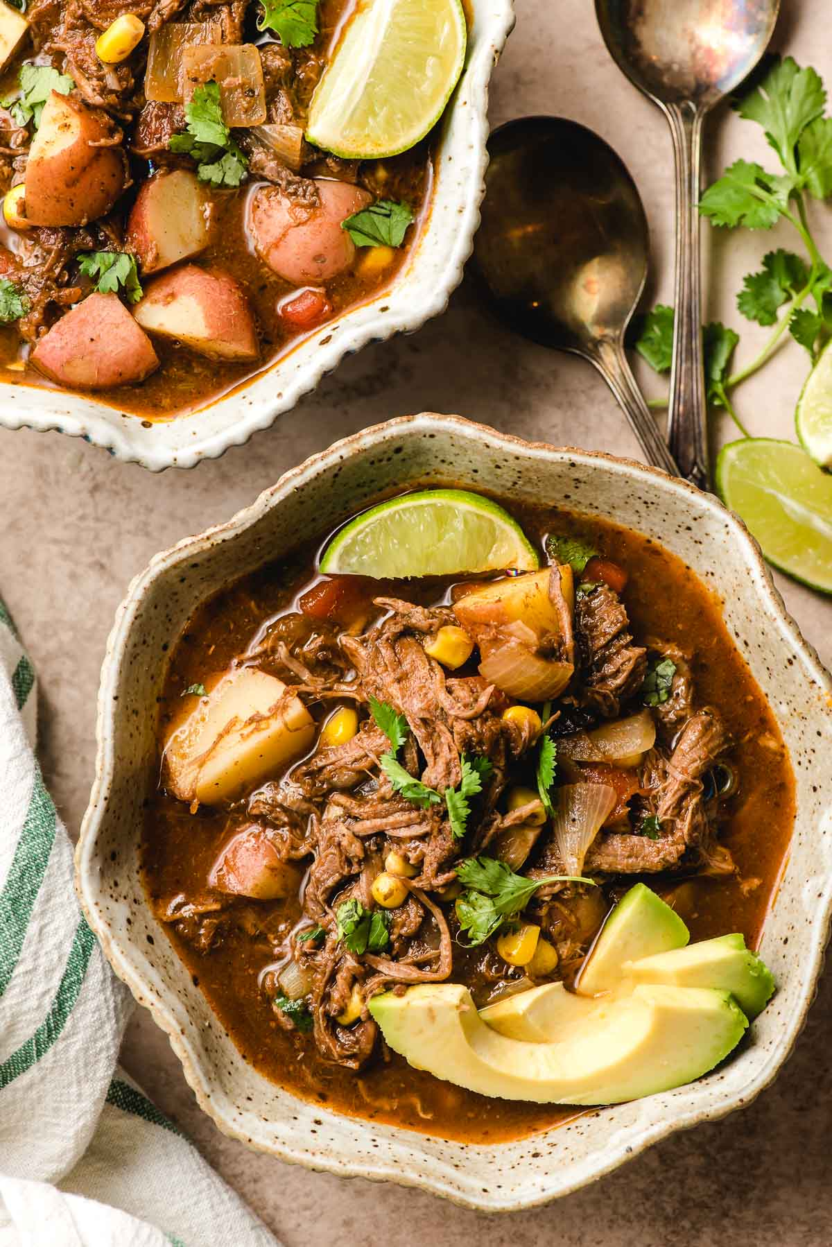 Scalloped bowl filled with Barbacoa Stew and garnished with lime wedges.