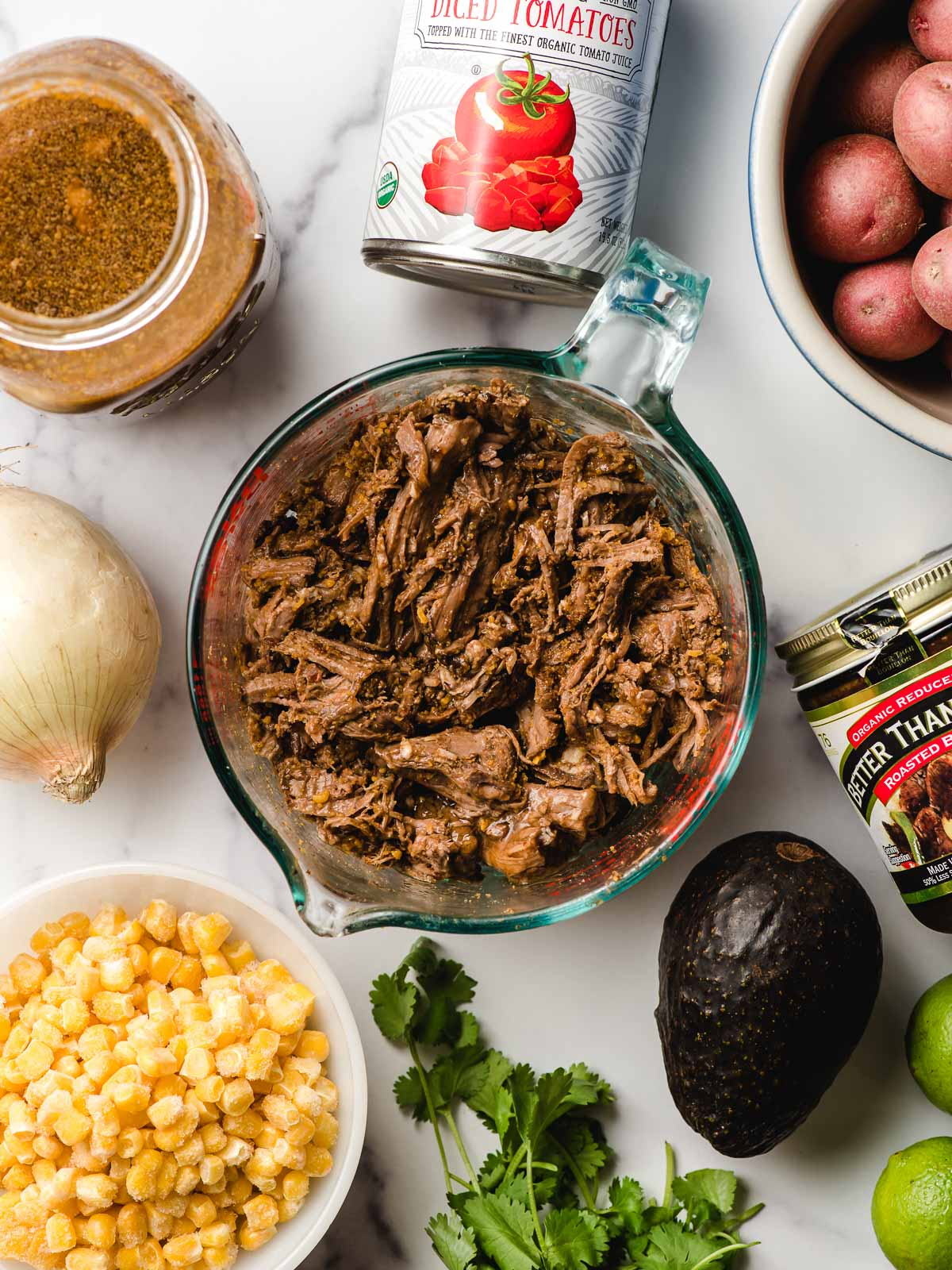 Ingredients for beef stew arranged on a white background- barbacoa beef, corn, cilantro, avocado, onion, broth, canned tomatoes, potatoes.
