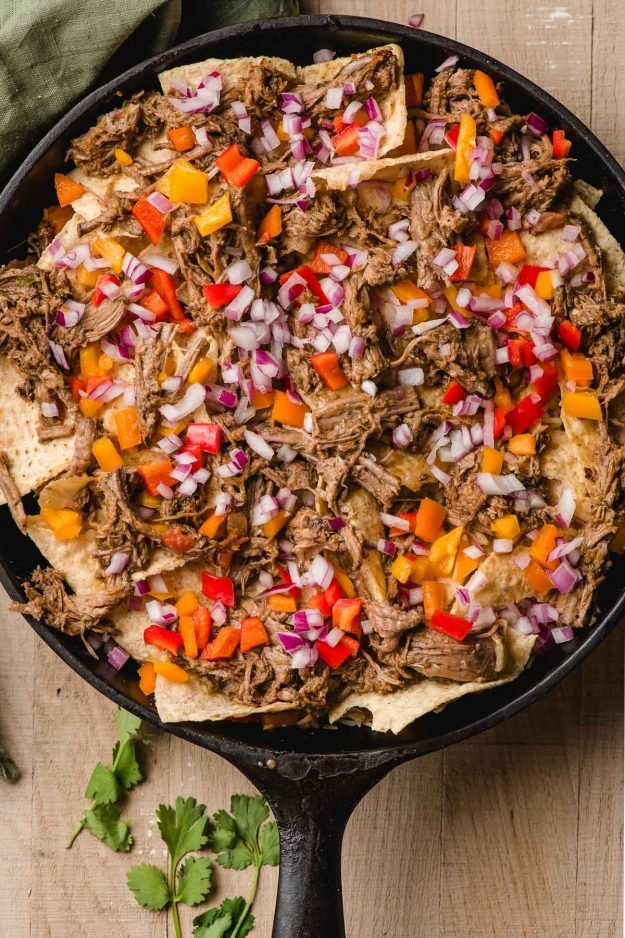 Skillet filled with tortilla chips, shredded beef, peppers, and onions.