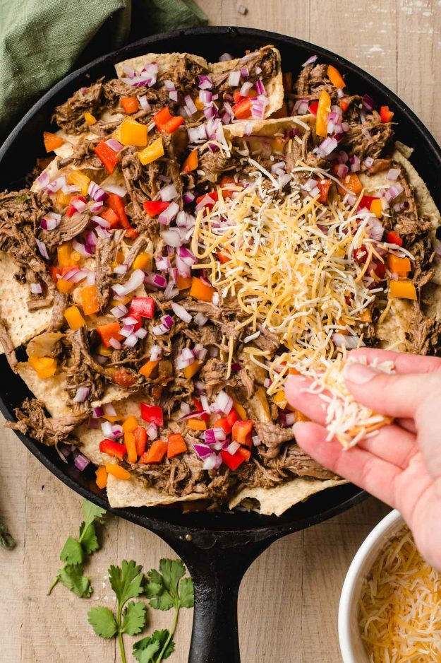 Hand sprinkling shredded Mexican cheese over a skillet full of nachos.