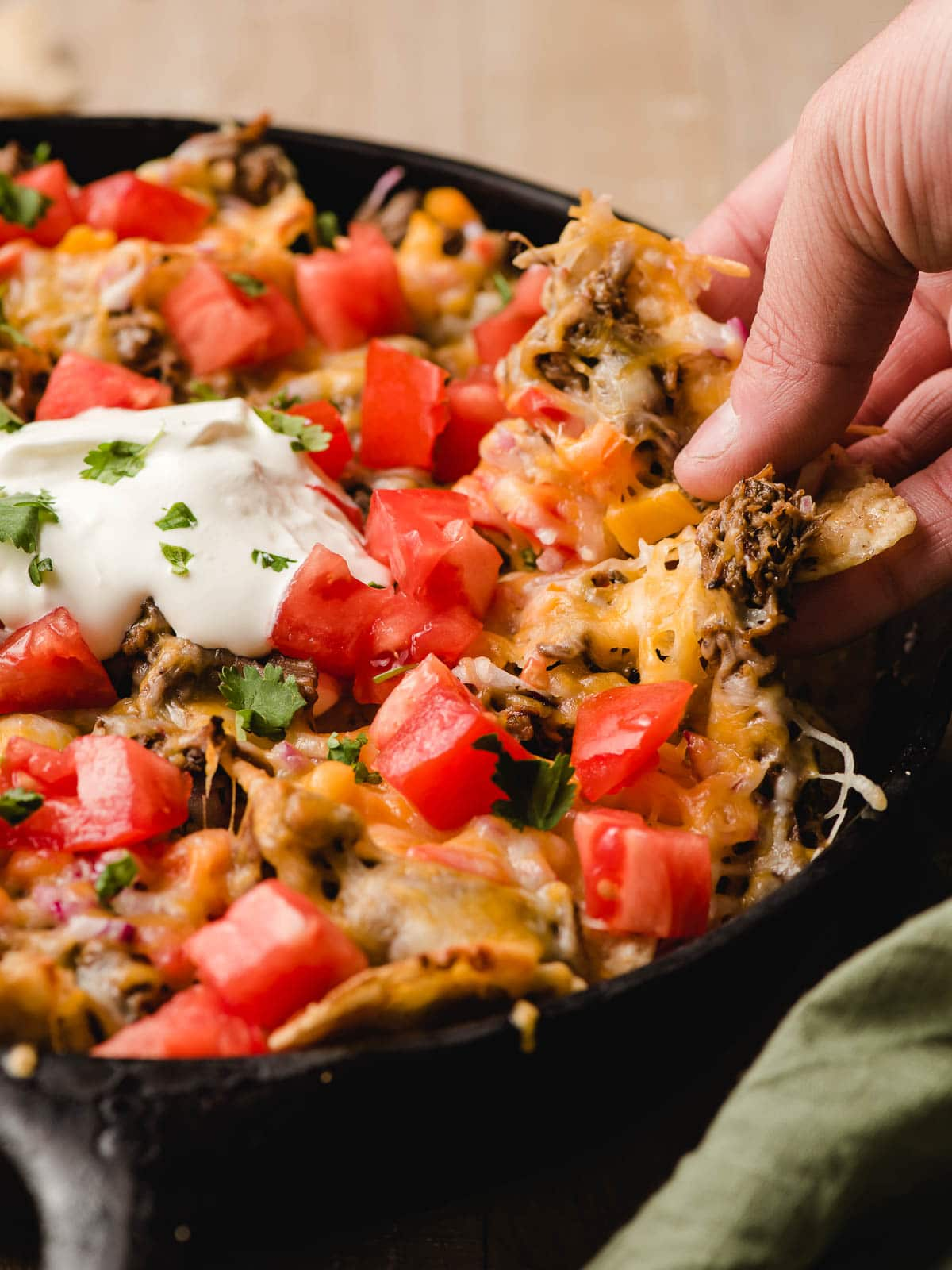Hand grabbing a nacho from a cast iron skillet.