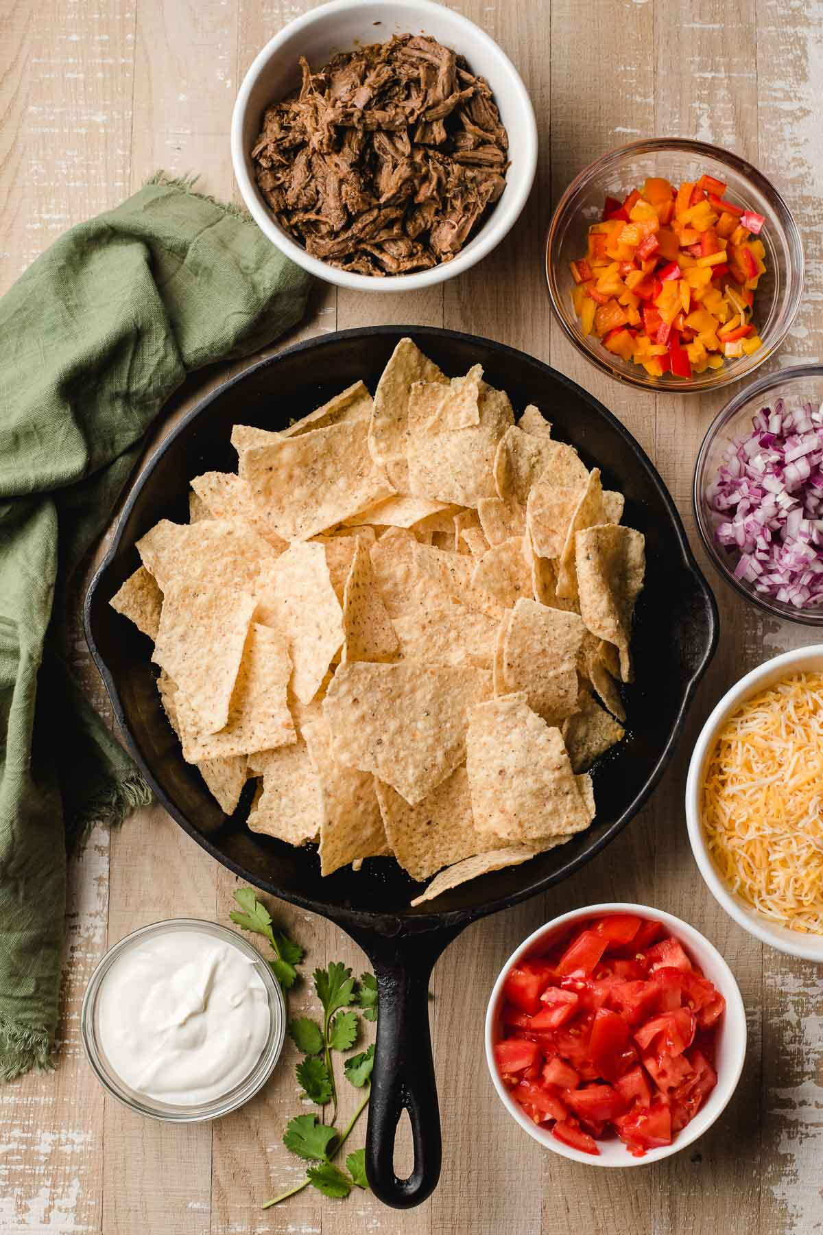 Ingredients for nachos, including a cast iron skillet filled with tortilla chips and bowl of cheese, tomatoes, onions, peppers, beef, and sour cream.