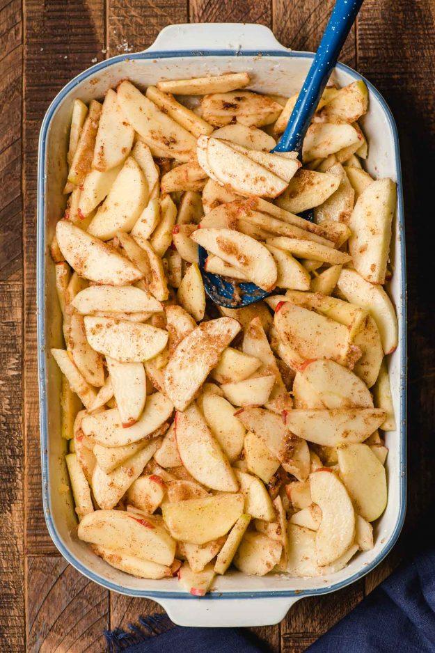 Uncooked cinnamon apple slices in a white casserole dish.