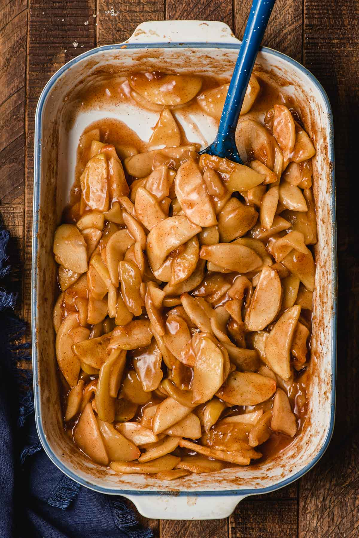 Spoon scooping cinnamon baked apples out of a white casserole dish.