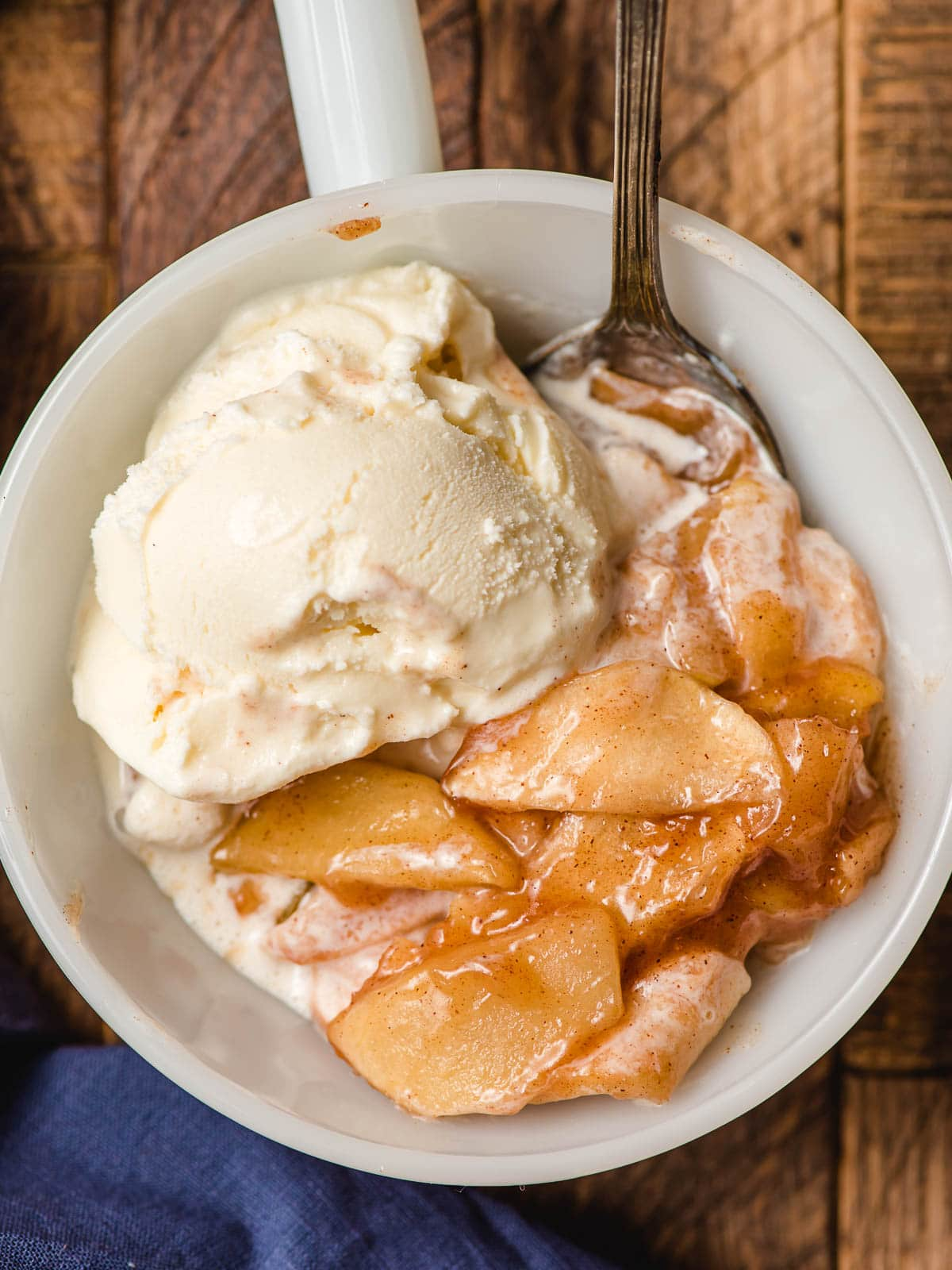 White bowl filled with warm cinnamon apples and a scoop of vanilla ice cream.