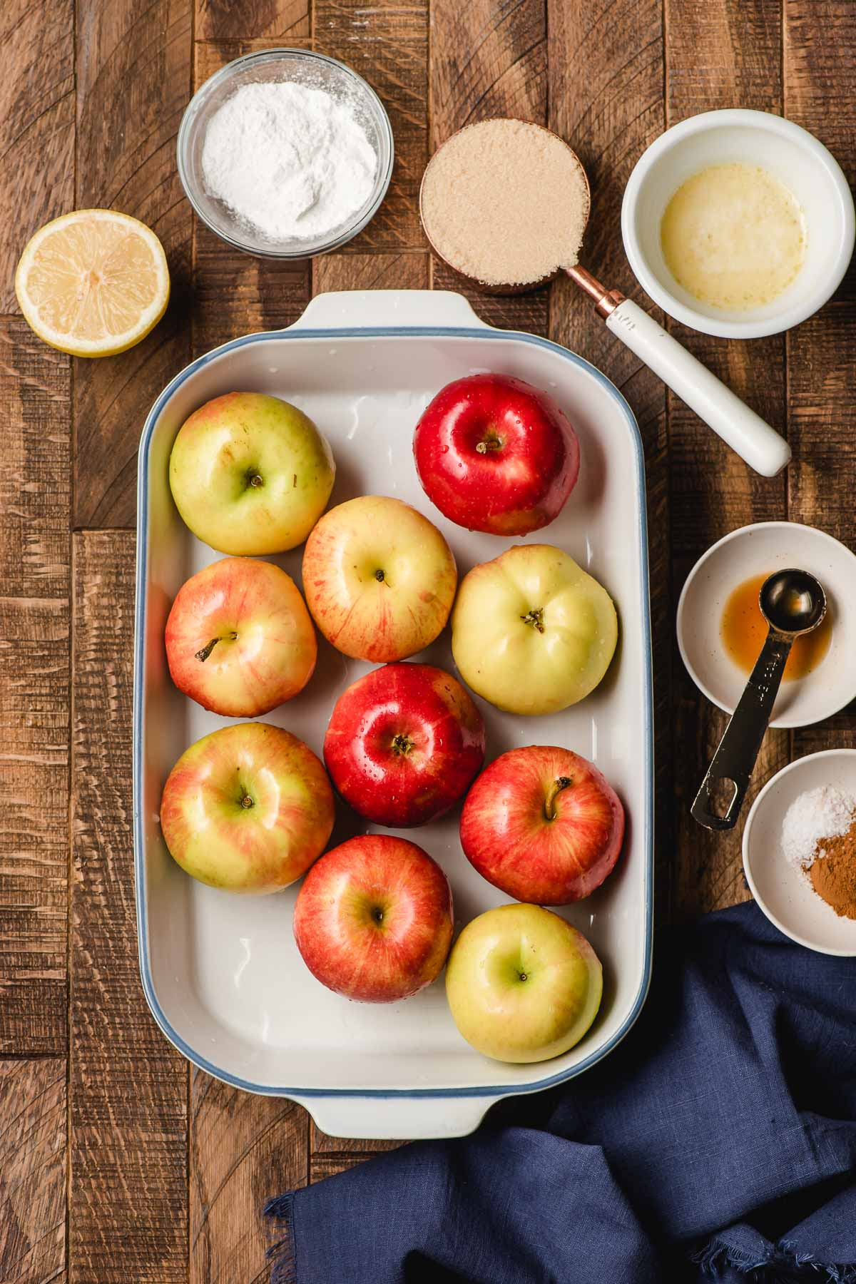 Whole apples in a casserole dish surrounded by bowls of brown sugar, melted butter, cornstarch, cinnamon, and a halved lemon.