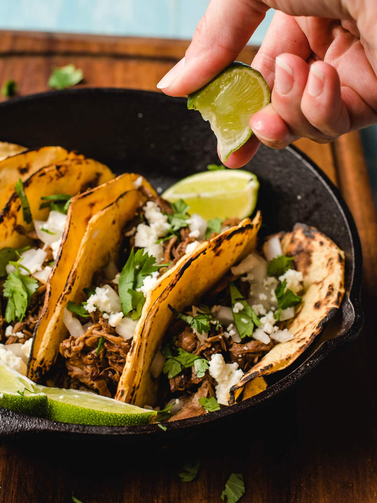 Hand squeeing lime onto barbacoa tacos.