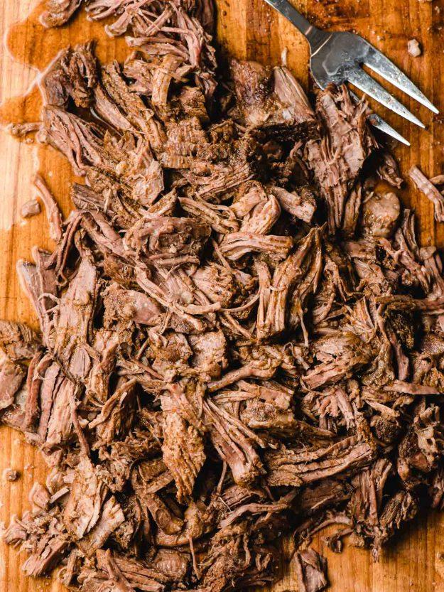 Shredded barbacoa beef on a wood cutting board.