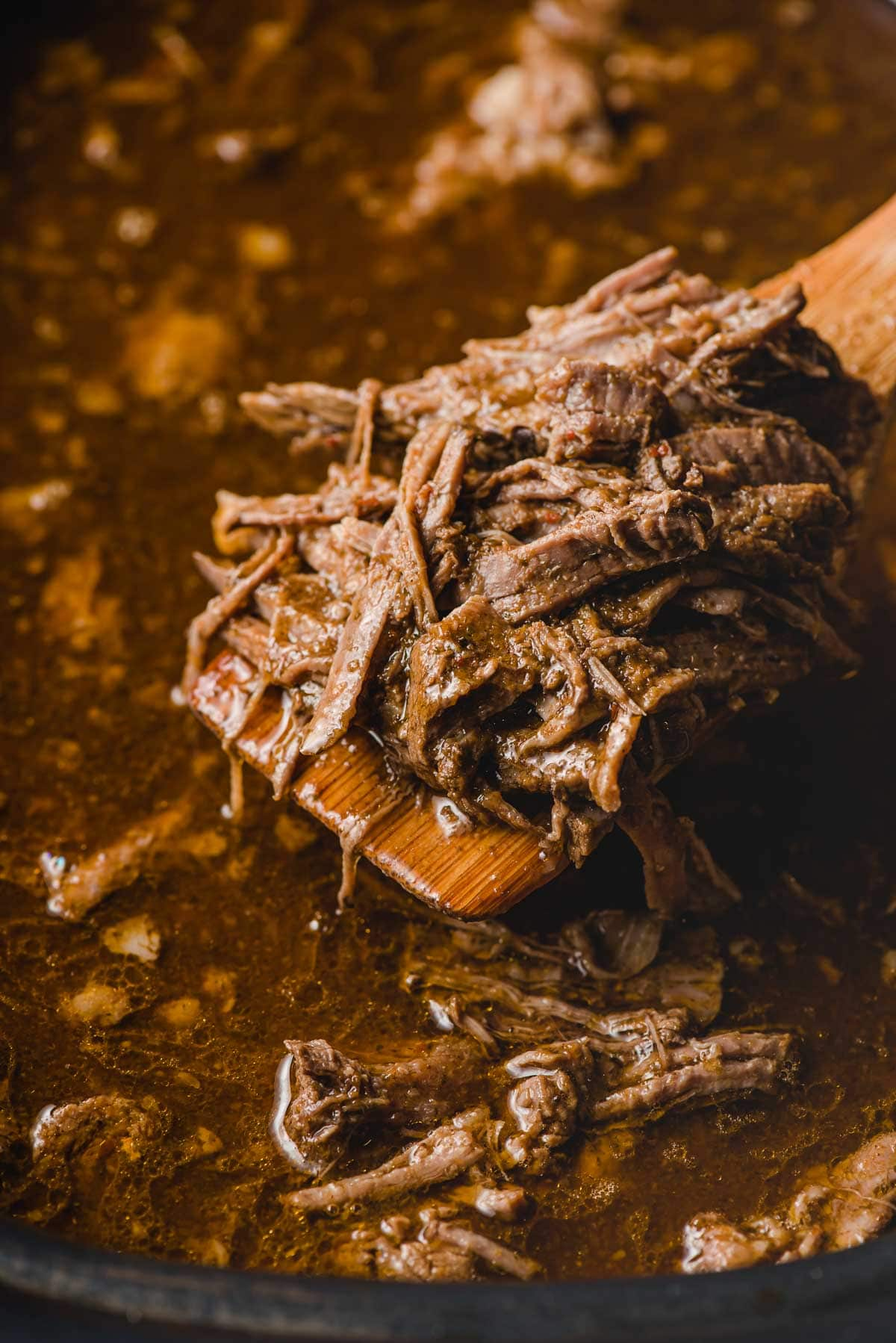 Wooden spoon scooping barbacoa out of a slow cooker.