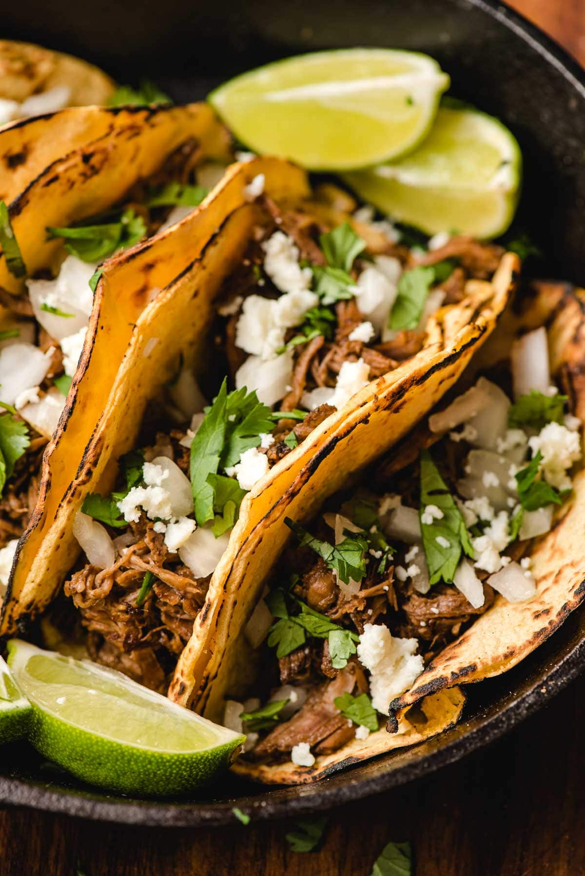 Crock Pot Barbacoa Tacos in a cast iron skillet with lime wedges.