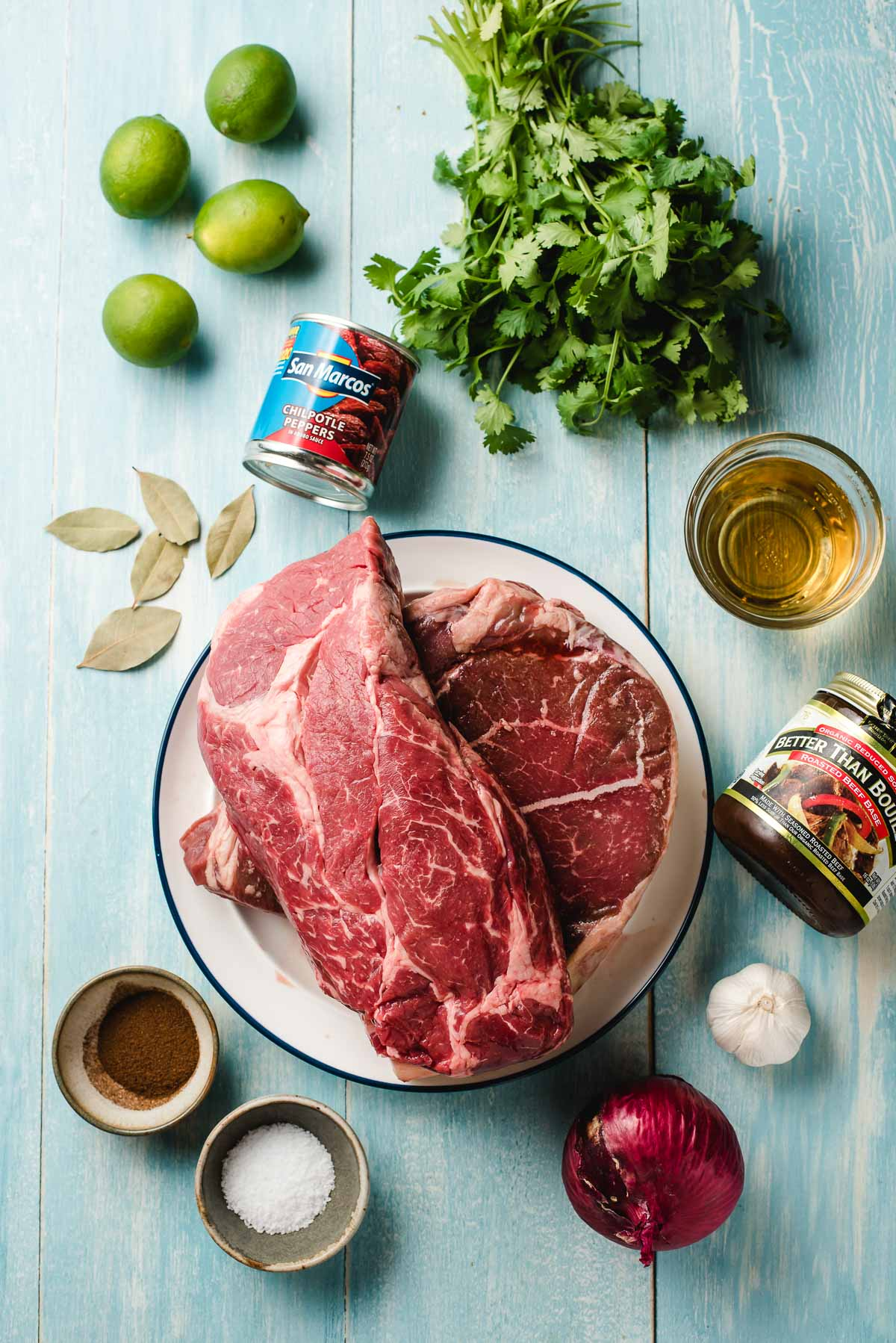 Ingredients for barbacoa beef on a light blue background- chuck roasts, salt, cumin and clove, lime, red onion, beef broth, cilantro, apple cider, chipotles in adobo.