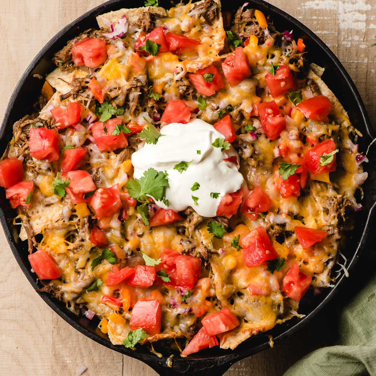 Cast Iron Skillet Nachos topped with beef, cheese, tomatoes, onions, sour cream, and cilantro.