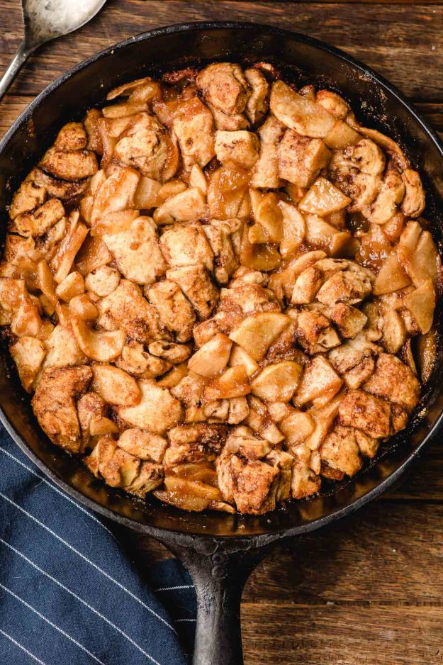 Baked cinnamon roll casserole in a cast iron skillet on a wood table.