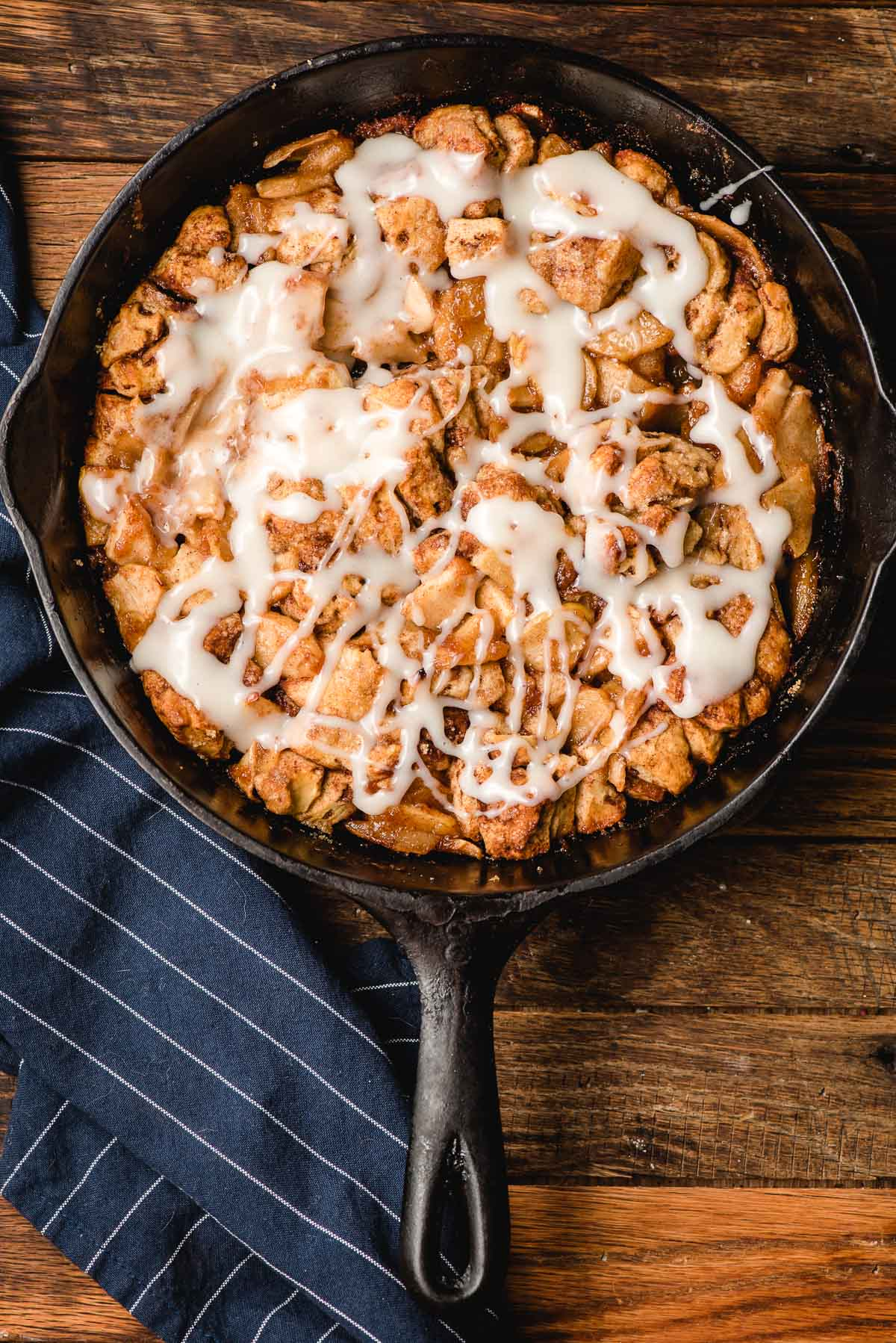 Cast iron skillet filled with apple cinnamon roll bake and covered with cream cheese frosting.