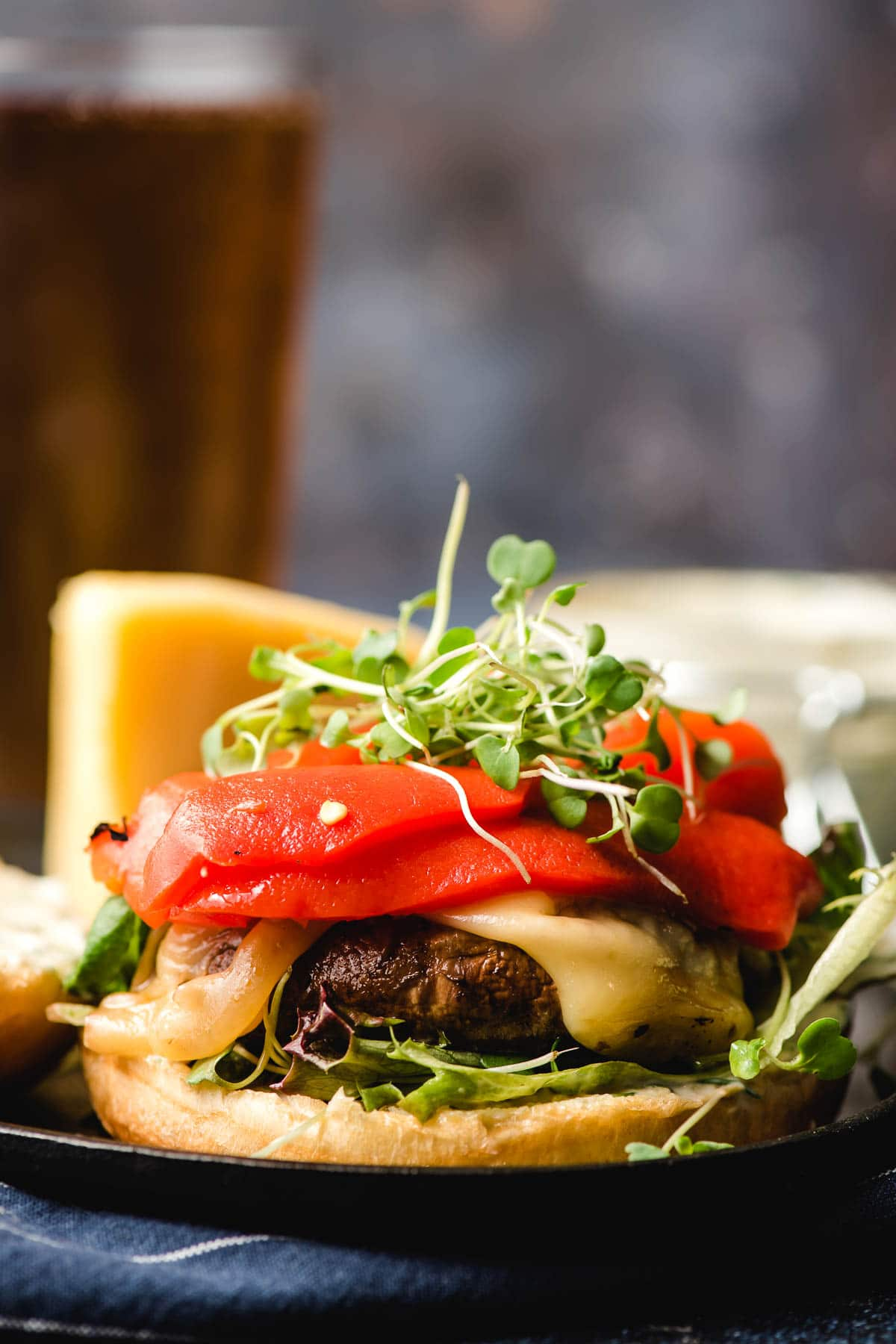Sandwich stacked with a marinated portobello mushroom, red pepper slices, and microgreens.