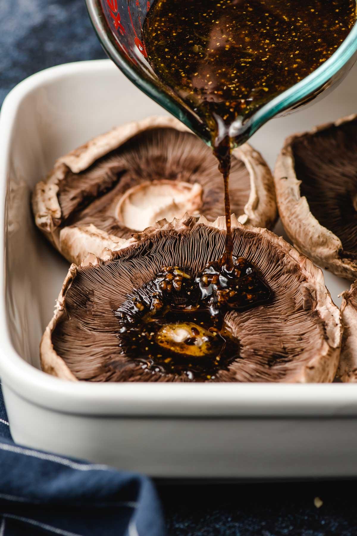 Balsamic marinade being poured onto a portobello mushroom.