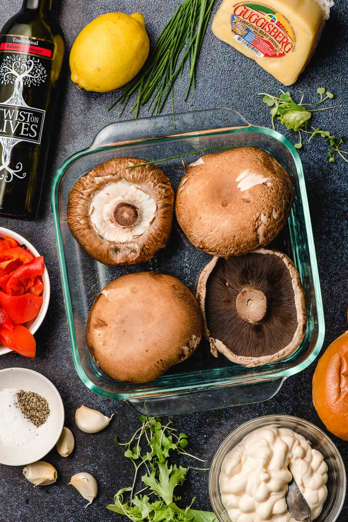 Portobello mushrooms in a glass casserole dish surrounded by ingredients for a sandwich.