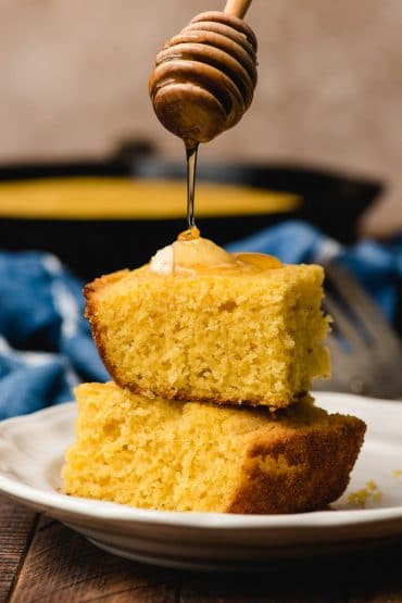 Honey dipper drizzling honey on a stack of cornbread slices.